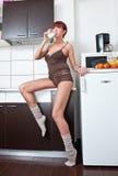 衬衣和袜子饮用奶的性感的妇女在厨房里 免版税库存图片