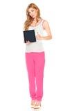 衬衣和裤子的女孩有片剂计算机的 免版税图库摄影