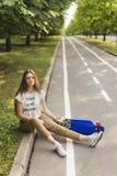 衬衣和长裤的女孩学生坐一张地毯在公园,在longboard旁边 溜冰板运动 户外 库存照片