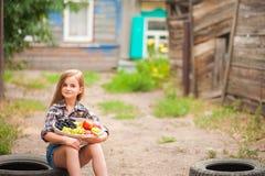 衬衣的与果子篮子的女孩和短裤  女孩农夫用苹果和葡萄 生态食物,人的概念 免版税库存照片