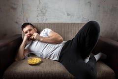 衬衣的人在长沙发说谎,吃着芯片并且观看体育渠道 懒惰的概念 库存图片