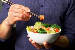 衬衣的人拿着有三文鱼、鲕梨、黄瓜、芝麻菜、硬花甘蓝、米、红萝卜、乳酪和chuha的捅碗与筷子 免版税库存图片