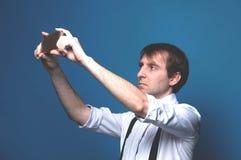 衬衣的人有滚动的站立和采取selfie的袖子和黑悬挂装置在蓝色背景 库存照片