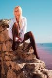 衬衣的在多岩石的海滩的金发碧眼的女人和袜子在海附近 免版税库存照片