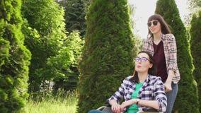 衬衣的女孩在公园伴随一个轮椅的女孩 他们沟通 影视素材
