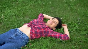 衬衣的少妇有说谎在草和身分的短的黑发的,微笑,在大学背景附近停放 影视素材