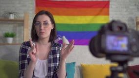 衬衣的年轻俏丽的妇女博客作者在LGBT纪录录影的旗子的背景 股票录像