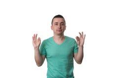 衬衣的快乐的年轻人打手势好标志的 库存照片
