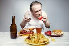 衬衣的更老的人吃破烂物不健康的饭食的 免版税库存照片