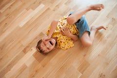 衬衣的滑稽的逗人喜爱的小男孩和在地板和笑上的短裤谎言 免版税图库摄影