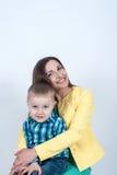 衬衣的男孩与妈妈坐轻的背景 库存照片