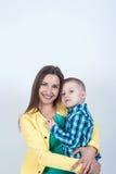 衬衣的男孩与妈妈坐轻的背景 免版税库存照片