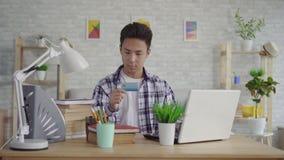 衬衣的画象年轻亚裔人输入与一万一银行卡的数据在膝上型计算机 影视素材