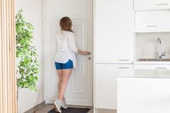 衬衣的看在窥视孔门的妇女和短裤,当某人按门铃 图库摄影