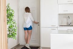 衬衣的看在窥视孔门的妇女和短裤,当某人按门铃 免版税图库摄影