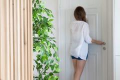 衬衣的看在窥视孔门的妇女和短裤,当某人按门铃 免版税库存照片