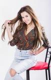 衬衣的美丽的女孩坐一张高脚椅子反对白色背景 热 在您的头发的风 微笑 免版税库存图片