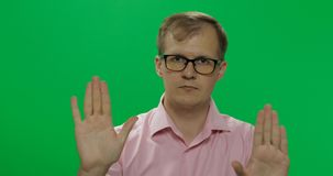 衬衣的英俊的年轻人反对和做中止姿态用手的 免版税图库摄影