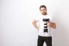 衬衣的年轻专业摄影师拿着与长的透镜的重的数字照相机 坚苦工作 免版税库存图片
