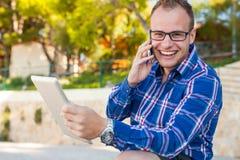 衬衣的年轻游人有在Croa的手机和片剂个人计算机的 免版税库存照片