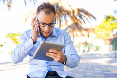衬衣的年轻游人有在Croa的手机和片剂个人计算机的 免版税库存图片