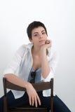 衬衣的年轻美丽的性感的微笑的女孩坐在白色背景隔绝的椅子,看照相机 图库摄影