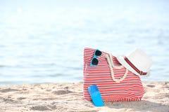 袋子、太阳镜和帽子在沙子在海附近 海滩对象 图库摄影