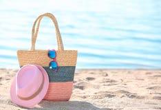 袋子、太阳镜和帽子在沙子在海附近 图库摄影