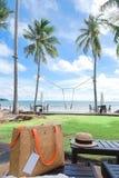 袋子和帽子在海滩供住宿与背景绿色领域,椰子tr 图库摄影
