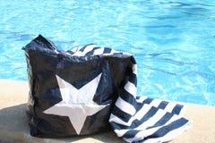 袋子和毛巾在游泳池旁边 免版税图库摄影