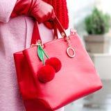袋子在女性手上 明亮的皮包 赞誉 桃红色外套和红色袋子 从毛皮的小装饰品樱桃 免版税库存照片