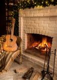 袋子看板卡圣诞节霜klaus ・圣诞老人天空 与在木柴地板上和诗歌选的壁炉驱散的明亮的火焰  附近吉他 库存照片