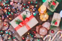 袋子看板卡圣诞节霜klaus ・圣诞老人天空 圣诞节曲奇饼巧克力,礼物,蜜桔,在迷离光背景的糖果 Xmas和新年快乐compositio 免版税库存照片