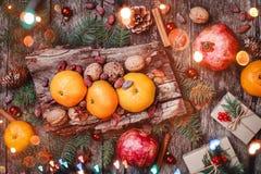 袋子看板卡圣诞节霜klaus ・圣诞老人天空 圣诞节礼物,石榴,蜜桔,坚果,可可子,冷杉在木多雪的背景分支 库存图片