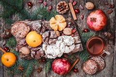 袋子看板卡圣诞节霜klaus ・圣诞老人天空 曲奇饼巧克力,茶,石榴,蜜桔,坚果,可可子,冷杉在木背景分支 图库摄影