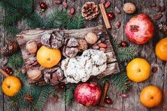 袋子看板卡圣诞节霜klaus ・圣诞老人天空 圣诞节礼物,曲奇饼巧克力,石榴,蜜桔,坚果,可可子,冷杉在木桌上分支 免版税库存照片