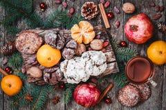 袋子看板卡圣诞节霜klaus ・圣诞老人天空 曲奇饼巧克力,茶,石榴,蜜桔,坚果,可可子,冷杉在木背景分支 免版税库存图片
