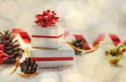 袋子看板卡圣诞节霜klaus ・圣诞老人天空 有红色弓、圣诞节球、红色丝带、锥体在白色背景与雪和光的圣诞礼物箱子 免版税库存图片