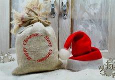 袋子礼物和圣诞老人帽子圣诞节魔术  免版税库存图片