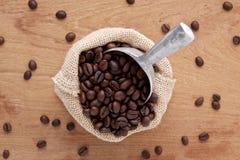 袋子褐色烤了与瓢的咖啡在木背景从 库存照片