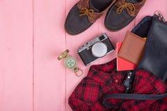 袋子,护照,照相机,指南针,鞋子,衬衣,在桃红色木背景的笔记本 免版税库存图片