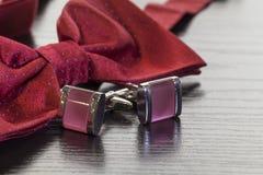 袖扣和红色蝶形领结 免版税库存照片
