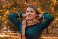 被上升一条的围巾的美丽的女孩在公园立场和她的朝向的手 免版税库存照片