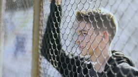 被丧失的青少年站立反对避难所,与哀伤的眼睛的神色金属栅格在世界 股票录像