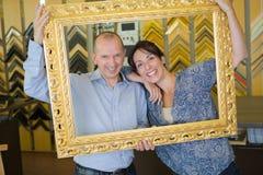 被买古色古香的金黄框架的愉快的夫妇 库存图片