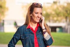 被享用的女孩特写镜头画象说在街道上的电话里 库存图片