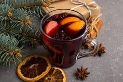 被仔细考虑的酒、一件礼物和香料在桌上在树旁边 圣诞节和新年,装饰的概念 免版税库存图片