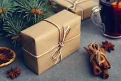 被仔细考虑的酒、一件礼物和香料在桌上在树旁边 圣诞节和新年,装饰的概念 库存照片