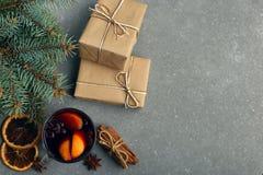 被仔细考虑的酒、一件礼物和香料在桌上在树旁边 圣诞节和新年,装饰的概念 库存图片