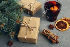 被仔细考虑的酒、一件礼物和香料在桌上在树旁边 圣诞节和新年,装饰的概念 免版税图库摄影